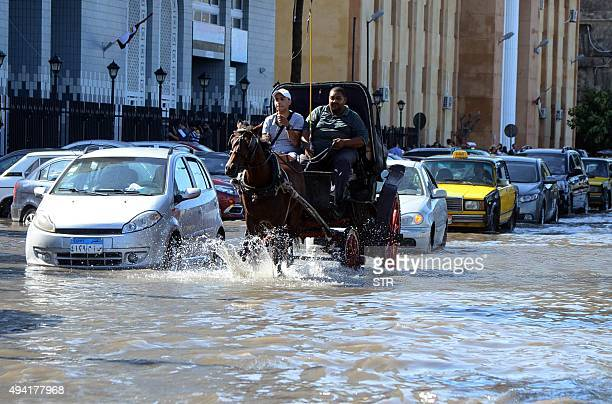 Egyptian men ride a horse carriage in a flooded street in Egypt's northern coastal city of Alexandria following heavy rains on October 25 2015 AFP...