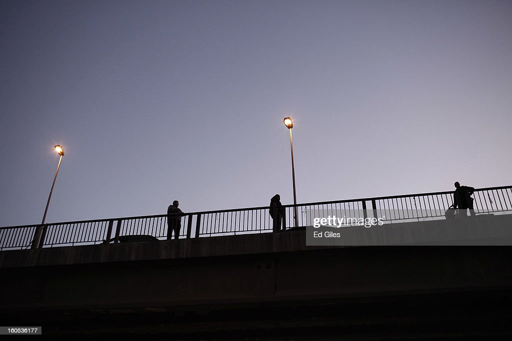 Egyptian men stand on a traffic overpass and watch a commemoration ceremony and march below (unseen) for a protester, killed during clashes with Egyptian security forces the previous night, at the Al Noor Mosque on February 2, 2013 in Cairo, Egypt. 23-year old protester Mohammed Hussein Korani was killed after sustaining gunshot wounds to the neck and chest during fighting with riot police outside Egypt's Presidential Palace in Cairo late on the night of February 1. Protests continued across Egypt nearly one week after the second anniversary of the Egyptian Revolution that overthrew former President Hosni Mubarak on January 25, 2011.(Photo by Ed Giles/Getty Images).