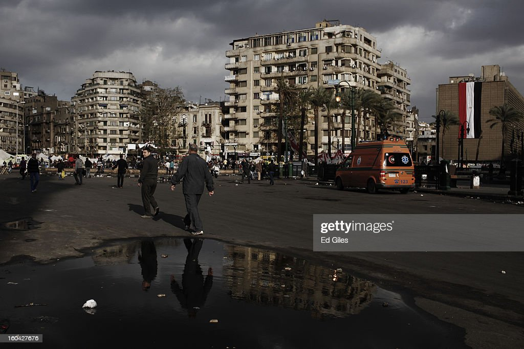 Egyptian men walk past a puddle of water on the road in Tahrir Square on January 31, 2013 in Cairo, Egypt. Protests continued across Egypt nearly one week after the second anniversary of the Egyptian Revolution that overthrew former President Hosni Mubarak on January 25, 2011. Further protests are expected over the coming weekend to commemorate the first anniversary of the Port Said football massacre, when over 70 fans of the Cairo-based Al Ahly football club were killed in a violent post-match brawl between fans of the opposing teams inside the Port Said football stadium after a match between the Al Ahly and Al Masry football teams.
