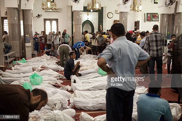 Egyptian men work to organise the bodies of supporters of deposed Egyptian President Mohammed Morsi killed during a violent crackdown by Egyptian...