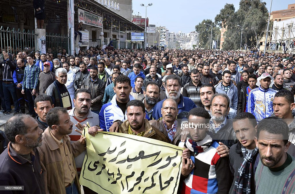 Egyptian mourners carry a placard reading in Arabic 'Port Said wants to trial the war criminal Morsi'' as they march in the canal city of Port Said on January 28, 2013 during the funeral of six people killed in clashes the day before, which were triggered after a court sentenced 21 people to death over a football riot that killed more than 70 people last year. A state of emergency came into force in three Egyptian provinces Port Said, Suez and Ismailiya which have been hit by deadly rioting, as President Mohamed Morsi scrambled to contain deepening divisions with calls for a national dialogue.