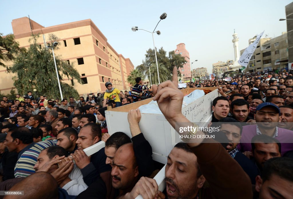 Egyptian mourners carry body of Abdelhalim Mehana who was killed during clashes with riot police on March 4, during his funeral procession in the Suez Canal city of Port Said on March 8, 2013, a day before a court is to issue verdicts over the killing of people in a football riot there. AFP PHOTO / KHALED DESOUKI