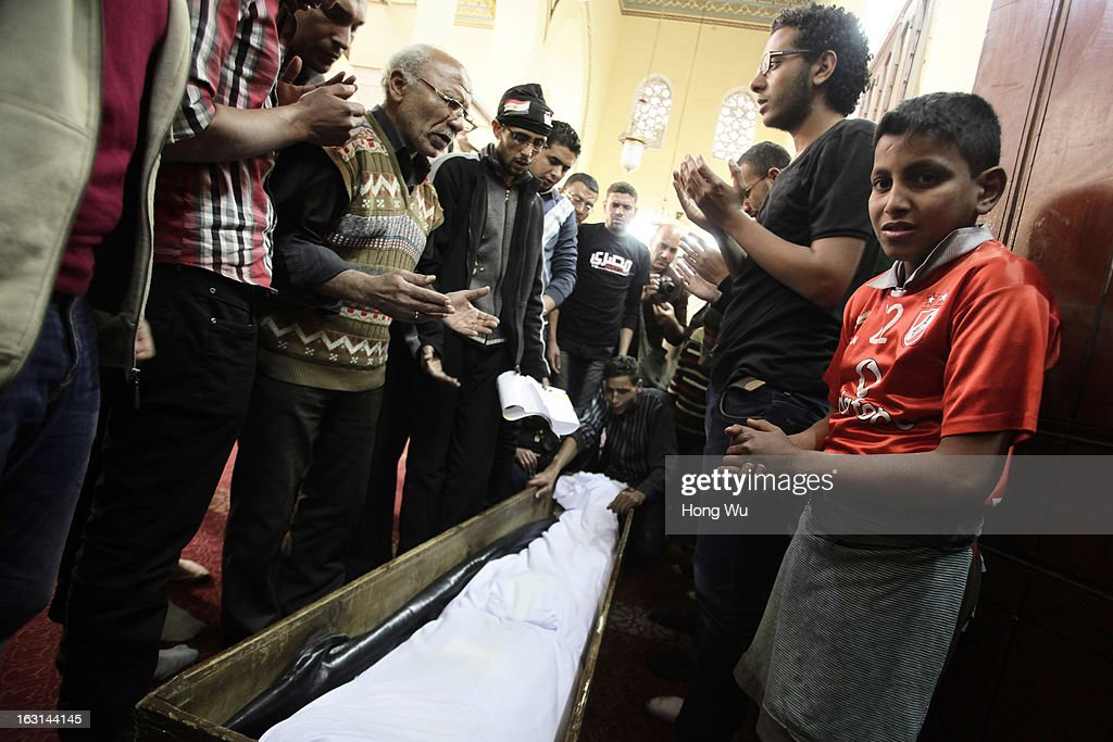 Egyptian mourners pray near the coffin of Mohamed Elshafee, who died during violence marking the second anniversary of Egyption uprising and was only recently identified, during his funeral on March 5, 2013 in Cairo, Egypt. Hundreds of protesters attend in the funeral and protest Egypt's President Mohamed Mursi.