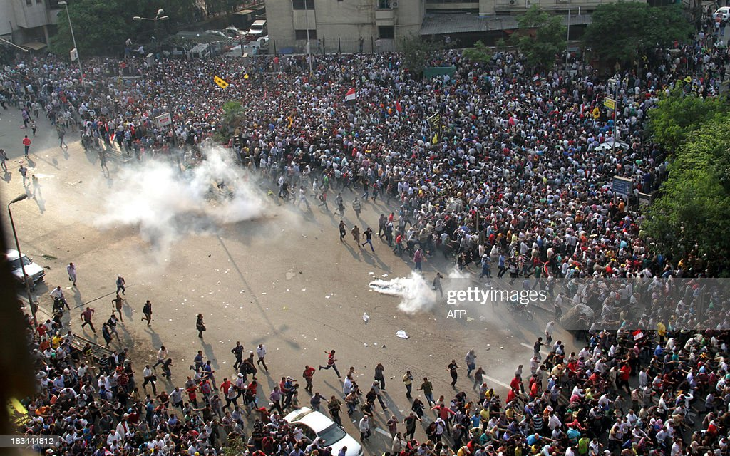 Egyptian Muslim brotherhood and supporters of ousted president Mohamed Morsi run for cover from tear gas during clashes with riot police along Ramsis street in downtown Cairo, on October 6, 2013. At least 28 people were killed in clashes between Islamists and police in Egypt, most of them in Cairo, a senior health ministry official said, as thousands of supporters of the military marked the anniversary of the 1973 Arab-Israeli war.