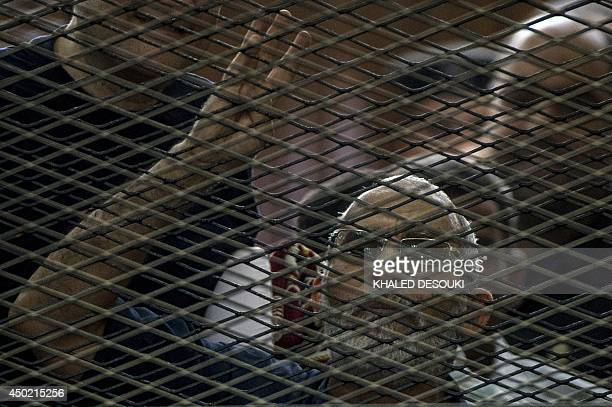 Egyptian Muslim Brotherhood leader Mohamed Badie gestures as he shouts from inside the defendants cage during his trial in the capital Cairo on June...