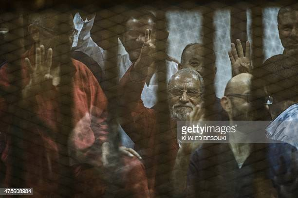 Egyptian Muslim Brotherhood leader Mohamed Badie gestures from the defendants cage as he and others attend their trial along with ousted president...
