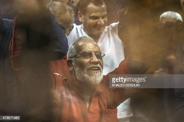 Egyptian Muslim Brotherhood leader Mohamed Badie raises his hands from behind the defendant's cage as the judge reads out the verdict sentencing him...