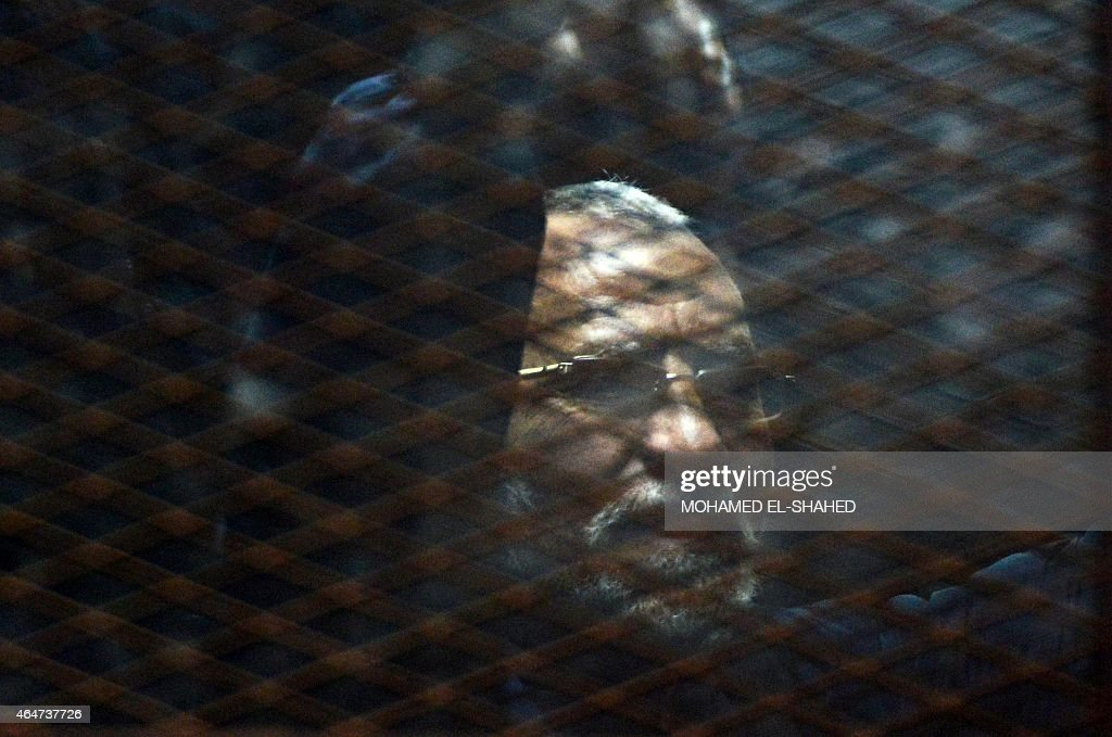 Egyptian Muslim Brotherhood leader Mohamed Badie stands behind bars during his trial at the non-commissioned police officers institute in the capital Cairo on 28 February, 2015. The court sentenced Badie to life imprisonment over the killing of protesters who stormed the group's Cairo headquarters in 2013. Three co-defendants of Badie were sentenced to death in the same trial. AFP PHOTO/ MOHAMED EL-SHAHED