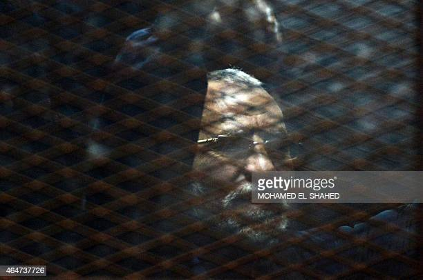 Egyptian Muslim Brotherhood leader Mohamed Badie stands behind bars during his trial at the noncommissioned police officers institute in the capital...
