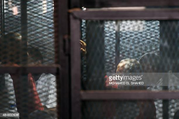 Egyptian Muslim Brotherhood leader Mohamed Badie stands behind bars along with MB members Mohamed alBeltagy and Safwat Hegazy during a trial in Cairo...