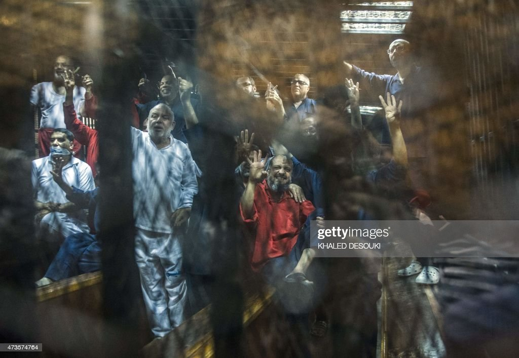 Egyptian Muslim Brotherhood top figure Mohamed elBeltagy gestures from behind the defendant's cage as the judge reads out the verdict sentencing him...