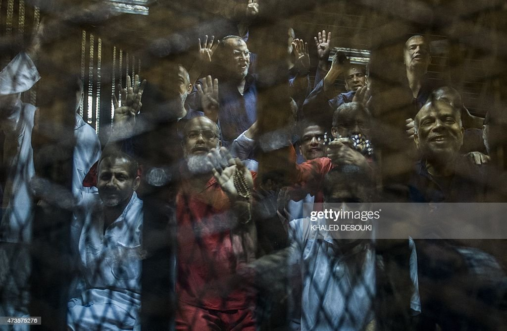 Egyptian Muslim Brotherhood top figure Saad alHusseini gestures from behind the defendant's cage as the judge reads out the verdict sentencing him...