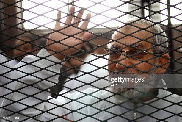 Egyptian Muslim Brotherhood's supreme guide Mohamed Badie waves from inside the defendants cage during the trial of Brotherhood members on February 3...