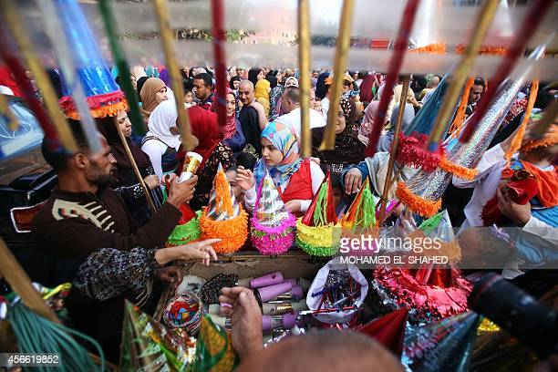 Egyptian Muslims families buy goods as they mark the first day of Eid alAdha or the Festival of Sacrifice which marks the end of the Hajj pilgrimage...