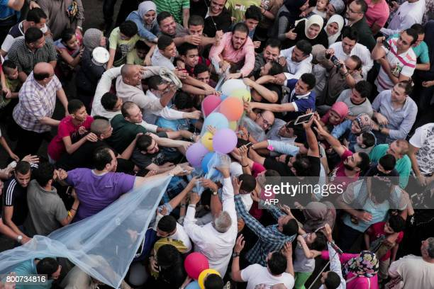 Egyptian Muslims release balloons at the end of prayers on the first day of Eid alFitr holiday that marks the end of the holy fasting month of...