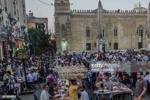 Egyptian Muslims sit on shared tables as they wait for the 'Iftar' meal to break their daylong fast during the holy month of Ramadan in Cairo khan...