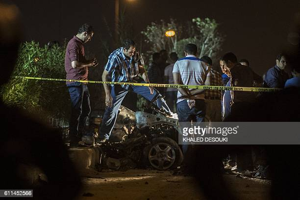 TOPSHOT Egyptian officials inspect the wreckage of a car bomb that exploded in a Cairo suburb after Egypt's deputy prosecutor general drove by late...