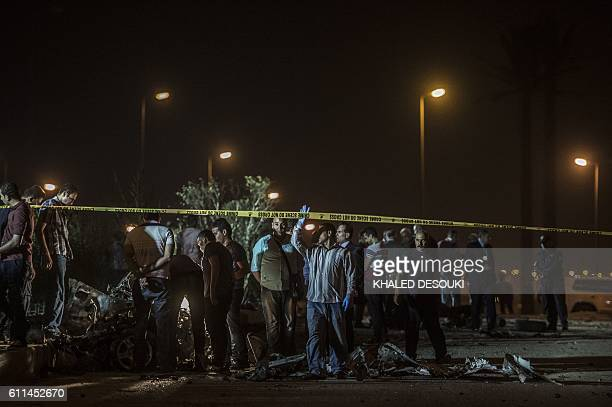 Egyptian officials inspect the wreckage of a car bomb that exploded in a Cairo suburb after Egypt's deputy prosecutor general drove by late on...