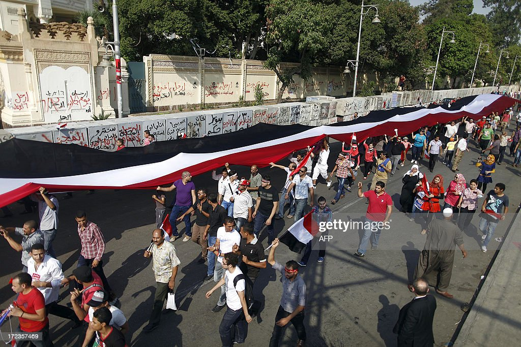 Egyptian opposition demonstrators calling for the ouster of President Mohamed Morsi holds high a long Egyptian flag as the march outside the presidential palace in Cairo on July 2, 2013. Egypt's political crisis deepened as Islamist President Morsi snubbed an army ultimatum threatening to intervene if he did not meet the demands of the people, and five ministers led a spate of government resignations.