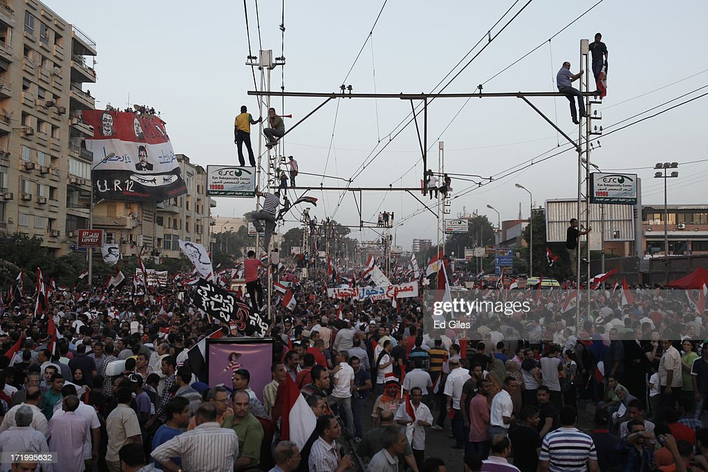 Egyptian opposition protesters fill a street during a demonstration at the Egyptian Presidential Palace as part of the 'Tamarod' campaign on June 30, 2013 in Cairo, Egypt. Crowds of pro- and anti-Morsi protesters gathered in locations across Egypt on June 30, the day of a series of nation-wide mass demonstrations entitled 'Tamarod', or 'Rebel', planned to take place on the first anniversary of Morsi's election to the Egyptian Presidency. The 'Tamarod' campaign, organised by a coalition of opposition political groups, aims to bring down the government of President Morsi through country-wide demonstrations. (Photo by Ed Giles/Getty Images).