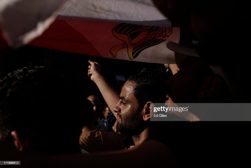 Egyptian opposition protesters hold an Egyptian flag above their heads during a demonstration in Tahrir Square as part of the 'Tamarod' campaign on June 30, 2013 in Cairo, Egypt. Crowds of pro- and anti-Morsi protesters gathered in locations across Egypt on June 30, the day of a series of nation-wide mass demonstrations entitled 'Tamarod', or 'Rebel', planned to take place on the first anniversary of Morsi's election to the Egyptian Presidency. The 'Tamarod' campaign, organised by a coalition of opposition political groups, aims to bring down the government of President Morsi through country-wide demonstrations. (Photo by Ed Giles/Getty Images).