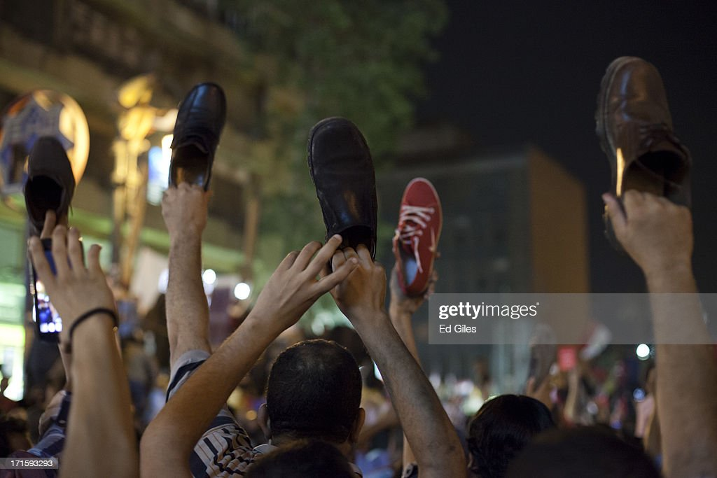 Egyptian opposition protesters hold their shoes in the air, an offensive gesture, during a demonstration in Tahrir Square against President Mohamed Morsi, prior to a televised national address by Morsi on June 26, 2013 in Cairo, Egypt. Protesters gathered in central Cairo's iconic Tahrir Square to watch a live speech by President Morsi just days prior to a series of planned nation-wide protests on June 30, the first anniversary of Morsi's election to the Egyptian Presidency. The 'Tamarod' or 'rebel' protests, organised by a coalition of opposition political groups, aim to bringing down the government of President Mohamed Morsi through country-wide protests.