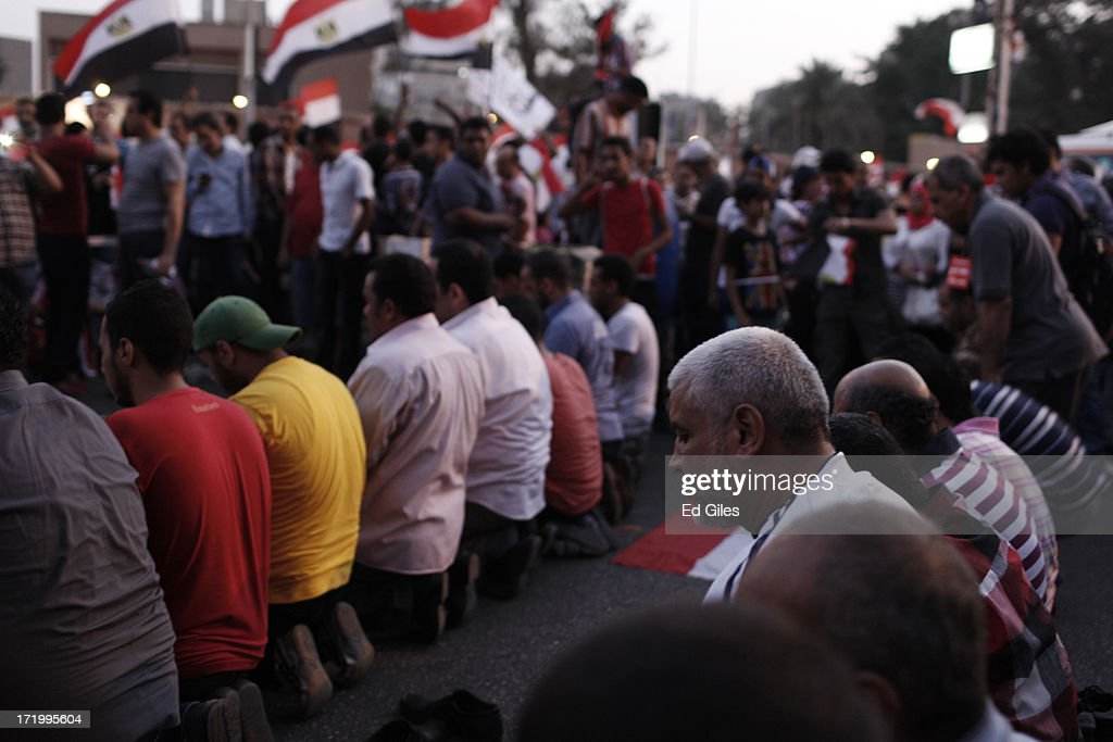 Egyptian opposition protesters perform evening prayers during a demonstration at the Egyptian Presidential Palace as part of the 'Tamarod' campaign on June 30, 2013 in Cairo, Egypt. Crowds of pro- and anti-Morsi protesters gathered in locations across Egypt on June 30, the day of a series of nation-wide mass demonstrations entitled 'Tamarod', or 'Rebel', planned to take place on the first anniversary of Morsi's election to the Egyptian Presidency. The 'Tamarod' campaign, organised by a coalition of opposition political groups, aims to bring down the government of President Morsi through country-wide demonstrations. (Photo by Ed Giles/Getty Images).