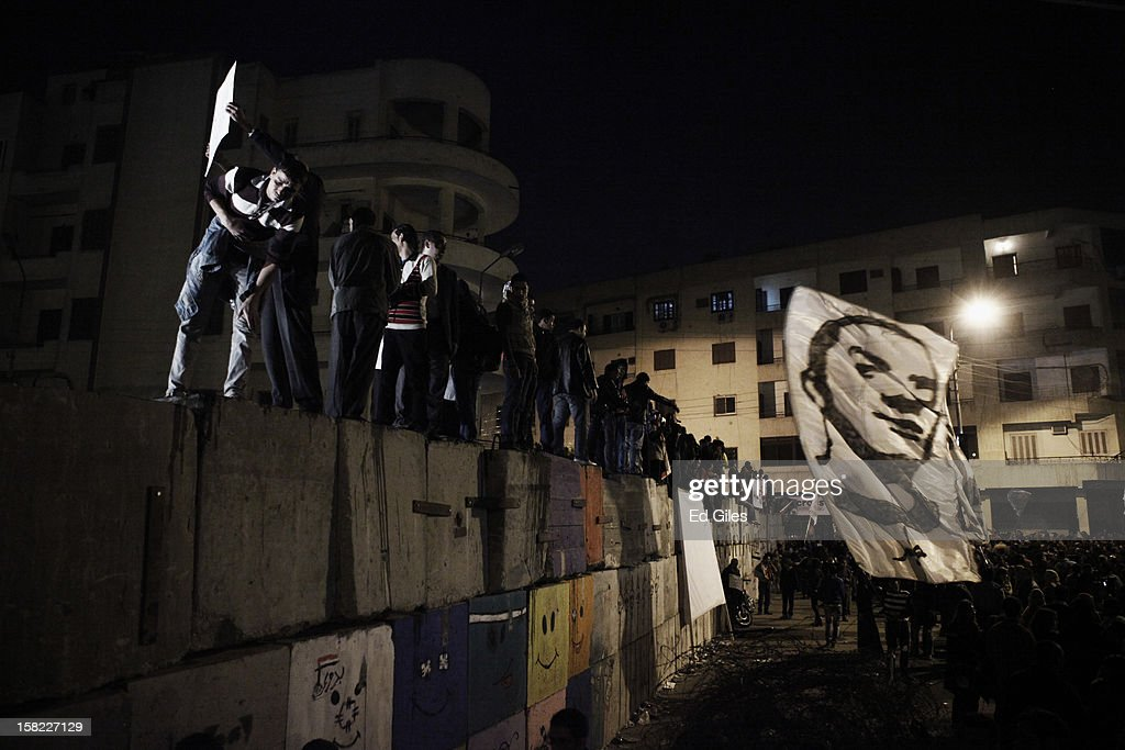 Egyptian opposition stand on top of a concrete wall built by Egyptian security forces in previous days outside Egypt's Presidential Palace during a demonstration against Egyptian President Mohammed Morsi on December 11, 2012 in Cairo, Egypt. Both Anti-Morsi and Pro-Morsi demonstrations continue across Egypt over the country's draft constitution, rushed through parliament in an overnight session on November 29. The country's new draft constitution, passed by a constitutional assembly dominated by Islamists, will go to a referendum on December 15. (Photo by Ed Giles/Getty Images).