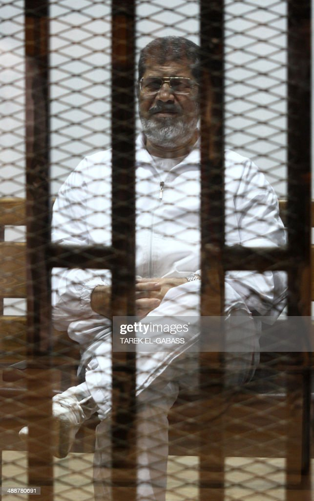 Egyptian ousted Islamist president <a gi-track='captionPersonalityLinkClicked' href=/galleries/search?phrase=Mohamed+Morsi&family=editorial&specificpeople=7484676 ng-click='$event.stopPropagation()'>Mohamed Morsi</a> looks on from behind the defendants cage during is trial on May 8, 2014 alongside 130 others on charges of organising jail breaks during the 2011 uprising that toppled strongman Hosni Mubarak.