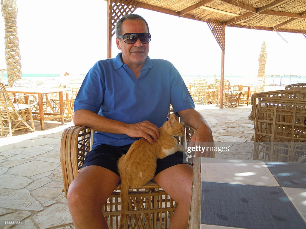 Egyptian owner of 'La Sirene' beach resort, Hussein al-Badrawi, poses with his cat on July 10, 2013 near Nuwaiba, on the East coast of Egypt's Sinai Peninsula. Many camps, which are operated by Bedouin tribes, are completely deserted as the number of visitors to the Peninsula has sharply declined due to the unrest riddling the country following the fall of Egypt's ousted president Mohamed Morsi, especially in the most northern parts of the Sinai.