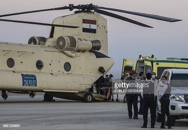 Egyptian paramedics load the corpses of Russian victims of a Russian passenger plane crash in the Sinai Peninsula into a military aircraft at Kabret...