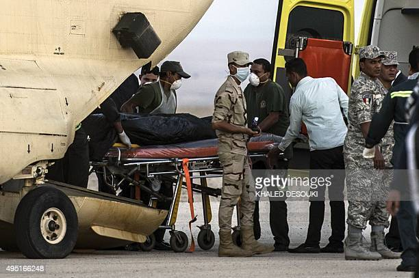 Egyptian paramedics load the corpses of Russian victims of a Russian passenger plane crash in the Sinai Peninsula into a military plane at Kabret...