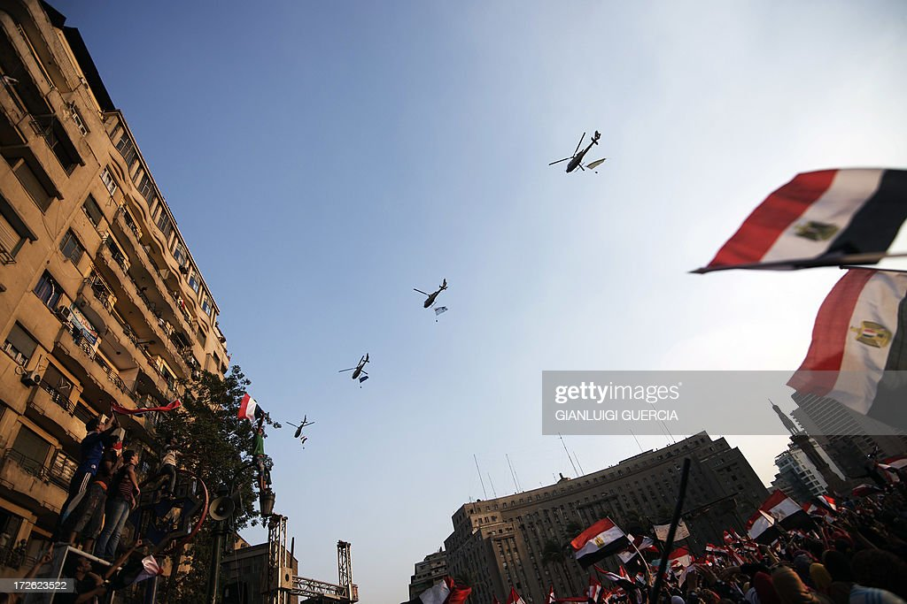 Egyptian people wave the national flag as army helicopters fly above Egypt's landmark Tahrir square on July 4, 2013. Egypt's Muslim Brotherhood, from which ousted president Mohamed Morsi hails, denounced a new 'police state' after the arrest of Islamist leaders and the closure of satellite channels. AFP PHOTO/GIANLUIGI GUERCIA
