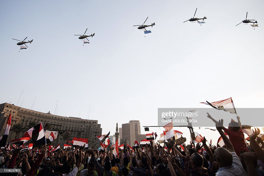 Egyptian people wave the national flag as army helicopters fly above Egypt's landmark Tahrir square on July 4, 2013. Egypt's Muslim Brotherhood, from which ousted president Mohamed Morsi hails, denounced a new 'police state' after the arrest of Islamist leaders and the closure of satellite channels.
