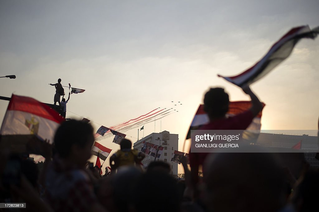 Egyptian people wave the national flag as army planes fly above Egypt's landmark Tahrir square on July 4, 2013. Egypt's Muslim Brotherhood, from which ousted president Mohamed Morsi hails, denounced a new 'police state' after the arrest of Islamist leaders and the closure of satellite channels.
