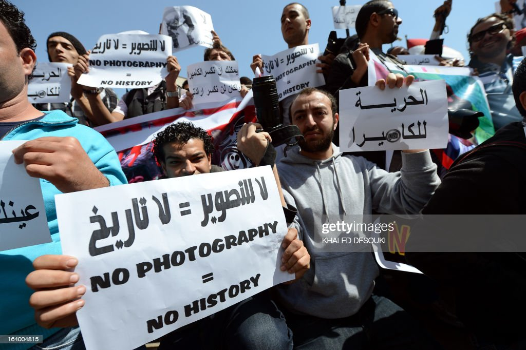 Egyptian photojournalists hold signs in English and Arabic, including one reading 'Freedom to the camera' (R), during a demonstration outside the Shura council in Cairo on March 19, 2013 to demand an end to harassment and attacks during their coverage of news. AFP PHOTO/POOL/KHALED DESOUKI
