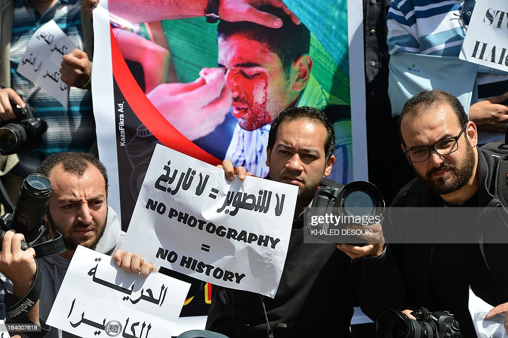 Egyptian photojournalists hold signs in English and Arabic, including one reading 'Freedom to the camera' (L), during a demonstration outside the Shura council in Cairo on March 19, 2013 to demand an end to harassment and attacks during their coverage of news.