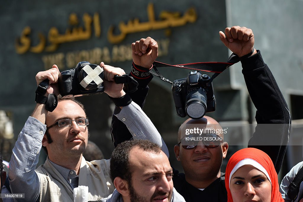 Egyptian photojournalists raise their cameras during a demonstration outside the Shura council in Cairo on March 19, 2013 to demand an end to harassment and attacks during their coverage of news.