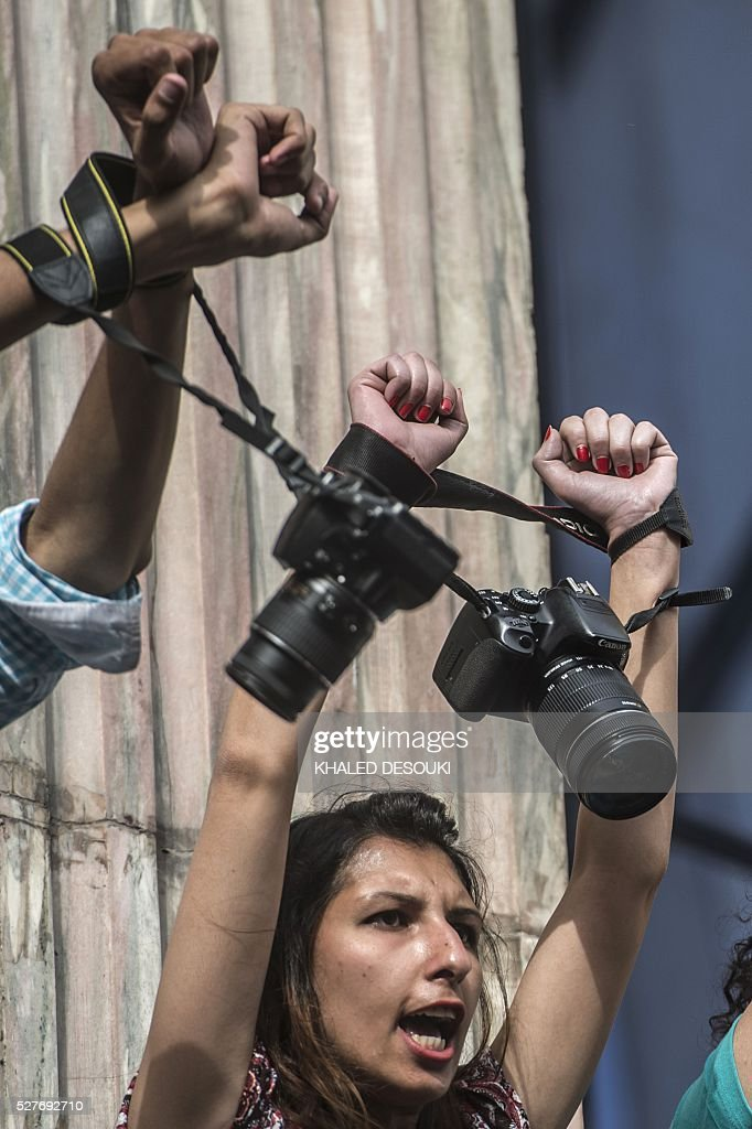 Egyptian photojournalists raise their cameras during a demonstration outside the Syndicate headquarters in Cairo on May 3, 2016 on the occasion of World Press Freedom day, a day after police stormed the headquarters of the journalists' association and arrested two journalists. Egyptian authorities on May 2 ordered the detention of two journalists for 15 days after their arrest on allegations of incitement to protest, a judicial source said. The decision comes a day after police stormed the headquarters of the journalists' association in central Cairo and arrested Amr Badr and Mahmud el-Sakka. A judicial source on Sunday said the pair had been wanted for alleged incitement to protest in violation of the law. / AFP / KHALED