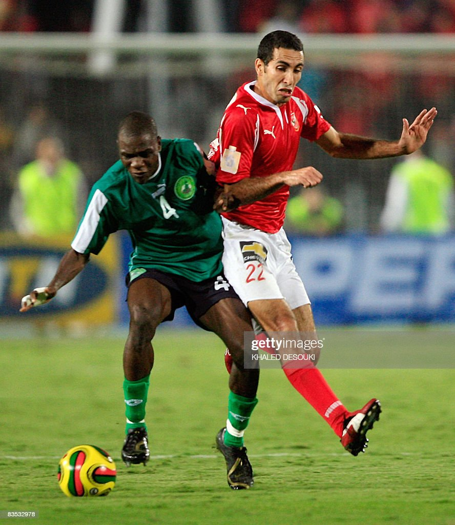 Egyptian player Mohammed Abu Trika of AlAhly club fights for the ball with Cameroons Cotonsport Garoua player Henri Minka during the African...