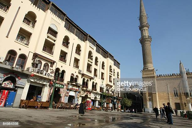 Egyptian police and few passersby walk in the usually busy plaza outside the AlHussein mosque on February 23 at the scene of a deadly bomb blast the...