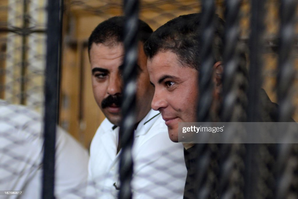 Egyptian police officers Awad Ismail Suleiman (L) and Mahmud Salah Amin, accused of using excessive force and killing 28-year-old blogger Khaled Said, sit behind bars in the defendants dock during their trial in Alexandria on October 1, 2013. Said is an Egyptian youth who died following police questioning before the revolution in 2010 in the most high profile case to have dominated headlines and sparked demonstrations in Egypt at the time.