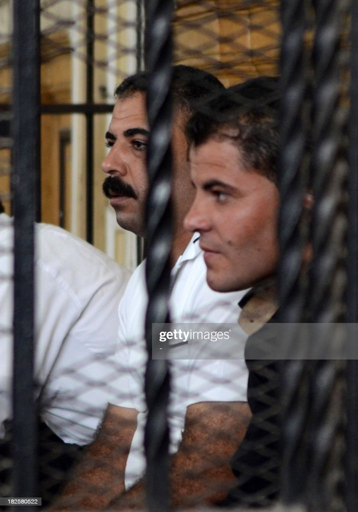 Egyptian police officers Awad Ismail Suleiman (L) and Mahmud Salah Amin, accused of using excessive force and killing 28-year-old blogger Khaled Said, sit behind bars in the defendants dock during their trial in Alexandria on October 1, 2013. Said is an Egyptian youth who died following police questioning before the revolution in 2010 in the most high profile case to have dominated headlines and sparked demonstrations in Egypt at the time. AFP PHOTO STR