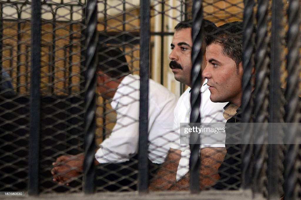 Egyptian police officers Awad Ismail Suleiman (L) and Mahmud Salah Amin, accused of using excessive force and killing 28-year-old blogger Khaled Said, sit behind bars in the dock during their trial in Alexandria on October 1, 2013. Said is an Egyptian youth who died following police questioning before the revolution in 2010 in the most high profile case to have dominated headlines and sparked demonstrations in Egypt at the time.