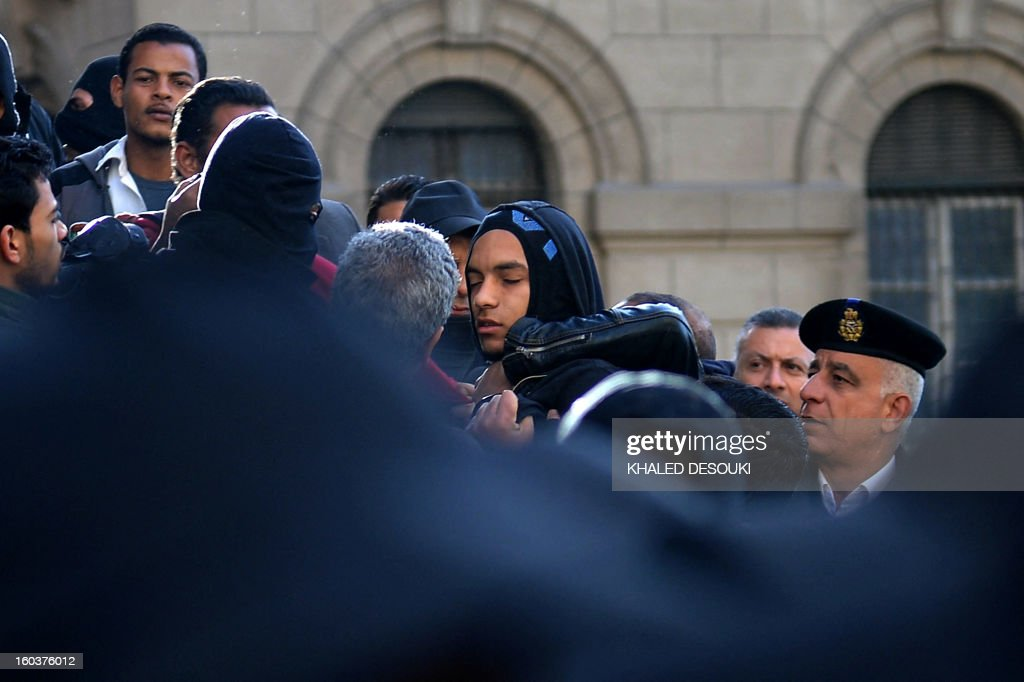 Egyptian policemen detain a youth (C) suspected of being a member of the 'Black Bloc' group during a demonstration outside the high court in central Cairo on January 30, 2013. Egyptian authorities detained suspected 'Black Bloc' members as they protested an order by the public prosecutor to arrest anyone from the shadowy opposition group, an AFP journalist said. Presenting themselves as the defenders of protesters opposed to President Mohamed Morsi's rule, the Black Bloc reportedly models itself on anarchist groups of the same name in Europe and the United States.