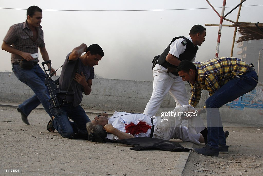 Egyptian policemen evacuate Giza security chief Nabil Farrag after he was shot during a raid in the village of Kerdassah on the outskirts of Cairo, on September 19, 2013. Farrag was killed when Egyptian security forces stormed Kerdassah in the latest crackdown on Islamist militants, security officials said.