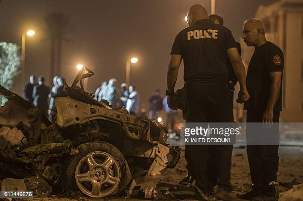Egyptian policemen inspect the wreckage of a car bomb that exploded in a Cairo suburb after Egypt's deputy prosecutor general drove by late on...