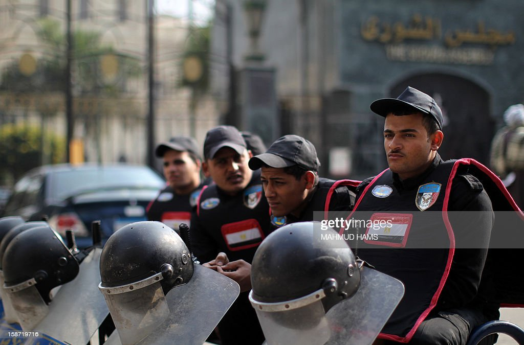 Egyptian policemen keep watch outside the Shura Council, the upper house of parliament where the Constituent Assembly drafted the country's new constitution, on December 26, 2012 in Cairo. Egyptian President Mohamed Morsi has signed into law a new constitution voted in despite weeks of opposition protests, but he was left facing an economic crisis and international disquiet over his rule. AFP PHOTO/MAHMUD HAMS