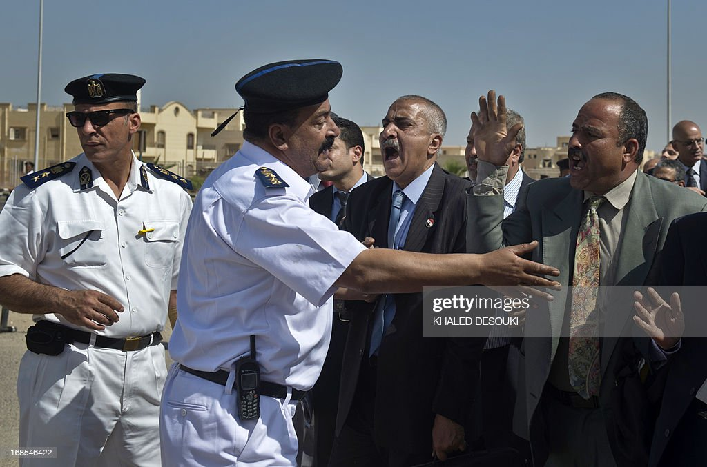Egyptian policemen (L) prevent lawyers to attend the retrial of former Egyptian president Hosni Mubarak outside the Egyptian police academy in Cairo, where Mubarak's trial is taking place on May 11, 2013. Mubarak appeared in court to face a new trial for complicity in the murder of hundreds protesters during the 2011 uprising.
