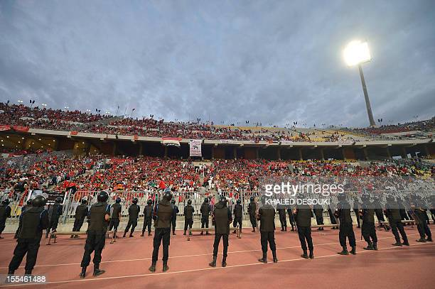 Egyptian policemen stand guard as fans cheer before AlAhly's football match against Tunisian team Esperance de Tunis during their CAF Confederation...